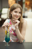 Young woman drinking cocktail in a cafe Royalty Free Stock Photos