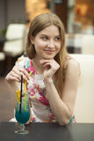 Young woman drinking cocktail in a cafe Royalty Free Stock Image