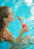 Young woman drinking cocktail in pool Stock Photography