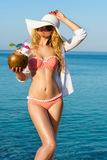 Young Woman drinking Coconut Cocktail at the beach. Summer Portrait of a Pretty girl dressed in swimsuit and white hat, holding fresh coconut cocktail Stock Images