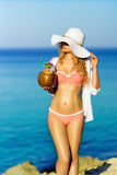 Young Woman drinking Coconut Cocktail at the beach. Summer Portrait of a Pretty girl dressed in swimsuit and white hat, holding fresh coconut cocktail Royalty Free Stock Images