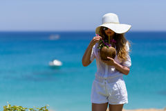 Young Woman drinking Coconut Cocktail at the beach. Summer Portrait of a Pretty girl dressed in white hat, holding fresh coconut cocktail Stock Images