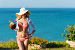 Young Woman drinking Coconut Cocktail at the beach. Summer Portrait of a Pretty girl dressed in white suit and hat with fresh coconut cocktail Royalty Free Stock Image