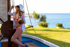 Young Woman drinking Coconut Cocktail at the beach. Summer Portrait of a Pretty girl dressed in white suit and hat sitting in a boat with fresh coconut Royalty Free Stock Photography