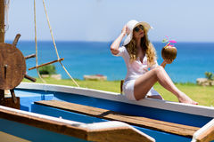 Young Woman drinking Coconut Cocktail at the beach. Summer Portrait of a Pretty girl dressed in white suit and hat sitting in a boat with fresh coconut Stock Photos