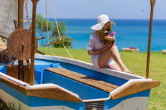 Young Woman drinking Coconut Cocktail at the beach. Summer Portrait of a Pretty girl dressed in white suit and hat sitting in a boat with fresh coconut Royalty Free Stock Images