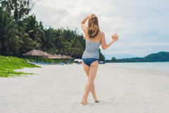 Young woman drinking coconut milk on beach. Stock Image