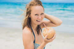Young woman drinking coconut milk on beach. Stock Photos