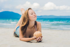 Young woman drinking coconut milk on beach. Stock Images