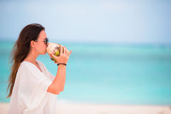 Young woman drinking coconut milk on the beach Stock Image