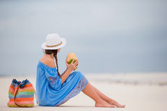 Young woman drinking coconut milk on the beach Royalty Free Stock Photo