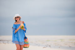Young woman drinking coconut milk on the beach Royalty Free Stock Photos