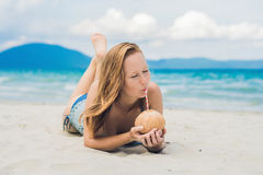 Young woman drinking coconut milk on beach. Dream scape Escape with beauty girl. The Benefits of Coconut Water Royalty Free Stock Photography