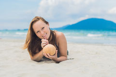 Young woman drinking coconut milk on beach. Stock Photography