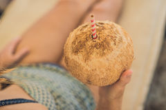 Young woman drinking coconut milk on Chaise-longue on beach. Royalty Free Stock Images