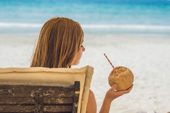 Young woman drinking coconut milk on Chaise-longue on beach. Dream scape Escape with beauty girl. The Benefits of Coconut Water royalty free stock images