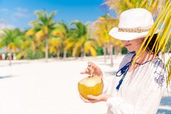 Young woman drinking coconut milk on hot day on the beach. Young woman drinking coconut milk during tropical vacation between palm trees stock photo