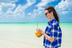 Young woman with coconut at tropical desert beach Stock Photo