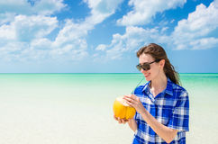 Young woman drinking coconut water at exotic beach Royalty Free Stock Photos