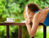 Young woman drinking cofee in a garden. Outdoors portrait.  Royalty Free Stock Images