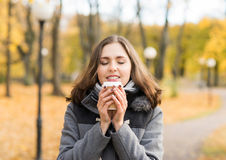 Young woman drinking coffee in an autumn park Stock Photos