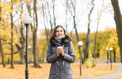 Young woman drinking coffee in an autumn park Royalty Free Stock Photos