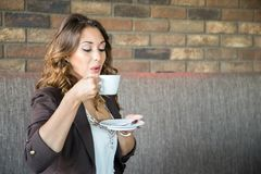 Young Woman Drinking Coffee. Beautiful young woman drinking coffee at a cafe Royalty Free Stock Images