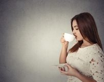 Young woman drinking coffee. Beautiful young woman drinking coffee isolated on gray wall background Stock Photos