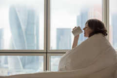 Young woman drinking coffee in bed Royalty Free Stock Images