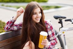 Young woman drinking coffee on a bicycle trip Stock Images