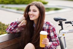 Young woman drinking coffee on a bicycle trip Stock Photography