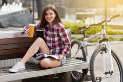 Young woman drinking coffee on a bicycle trip royalty free stock photos