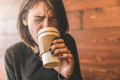 Young woman drinking a coffee and burning her tongue Royalty Free Stock Images