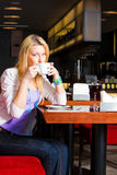 Young Woman Drinking Coffee in Cafe Royalty Free Stock Image