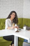 Young woman drinking coffee in cafe Stock Image
