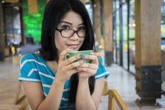 Young woman drinking coffee at cafe Stock Photo