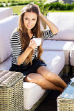 Young woman drinking coffee in a cafe outdoors Royalty Free Stock Photo