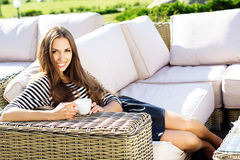Young woman drinking coffee in a cafe outdoors Royalty Free Stock Photography