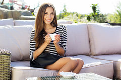 Young woman drinking coffee in a cafe outdoors Stock Photography
