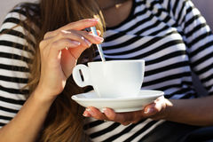 Young woman drinking coffee in a cafe outdoors Stock Image