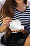 Young woman drinking coffee in a cafe outdoors Royalty Free Stock Image