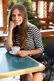 Young woman drinking coffee in a cafe outdoors Royalty Free Stock Photos