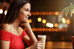 Young woman drinking coffee in a cafe Stock Photos
