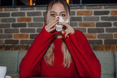 Young woman drinking coffee in a cafe royalty free stock images