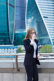 Young woman drinking coffee in front of business center Royalty Free Stock Photos