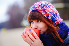 Young woman drinking coffee from her thermos, enjoying autumn evening by the sea Royalty Free Stock Photos