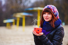 Young woman drinking coffee from her thermos, enjoying autumn evening by the sea Stock Photo