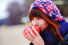 Young woman drinking coffee from her thermos, enjoying autumn evening by the sea Royalty Free Stock Photography