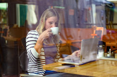 Young woman drinking coffee inside a cafeteria Stock Photography