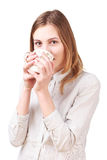 Young woman drinking coffee isolated on white. Young pretty woman drinking coffee isolated on white background Stock Photography